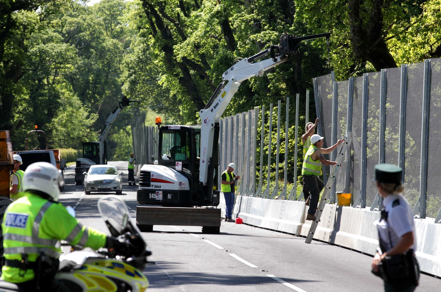 Police watch as a security fence is put in place at the Lough Erne resort for the G8 summit.