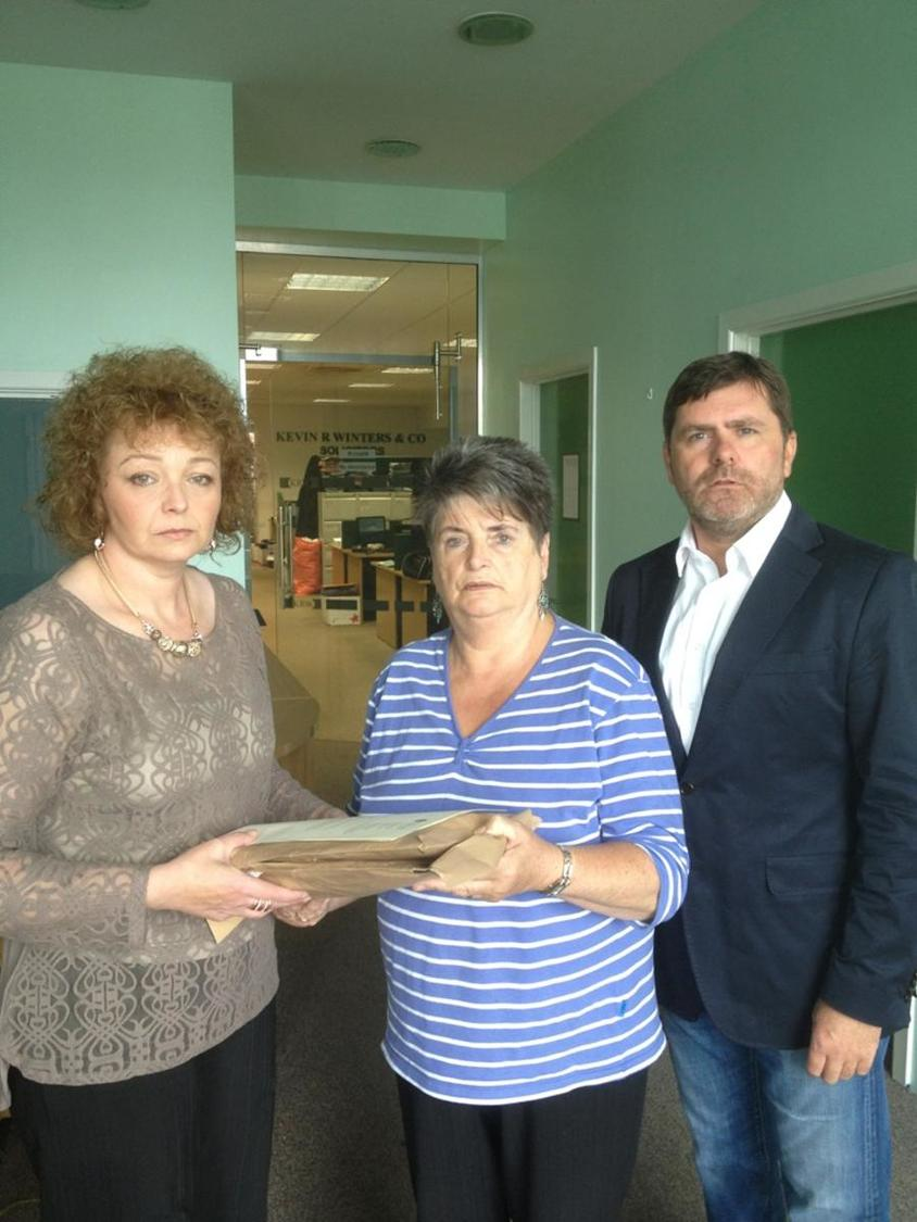 DCAL minister Ní Chuilín hands over PRONI papers to RFJ's Clara Reilly and Mark Thompson on Friday