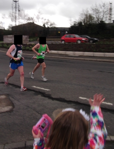 Marathon runners pass Ronan Kerr's car hours before the policeman was killed by an undercar bomb