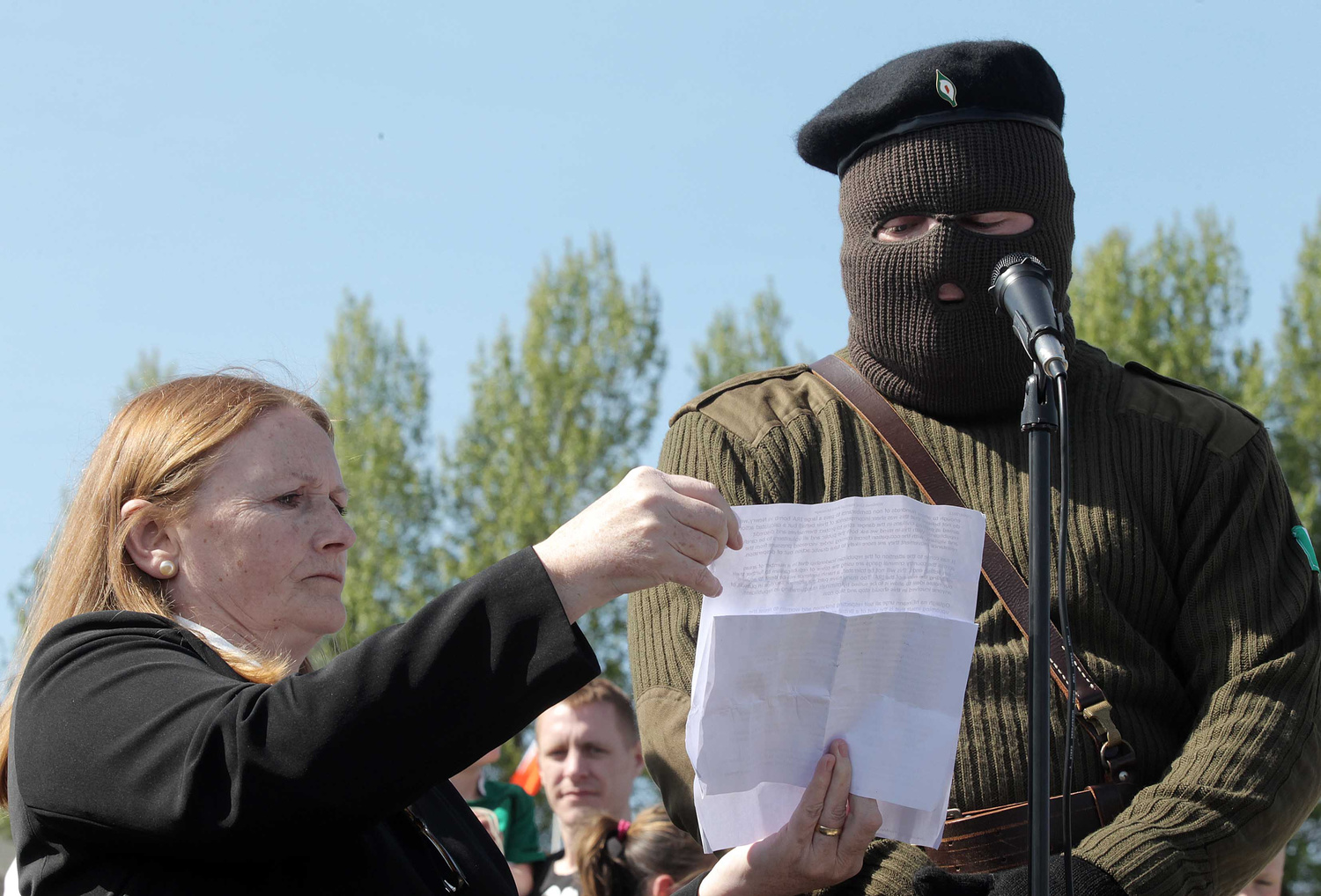 Marian Price holds a statement which is read by a masked RIRA man in Derry