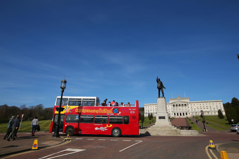 A bus tour passes the Stormont parliament