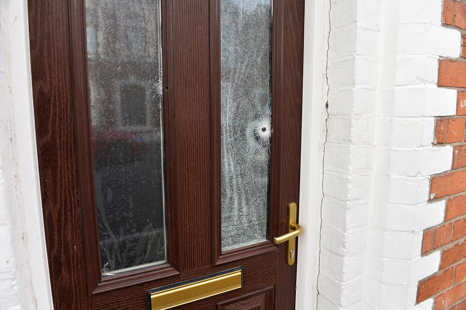 A bullet hole in the front door of a home. Picture credit Press Eye.