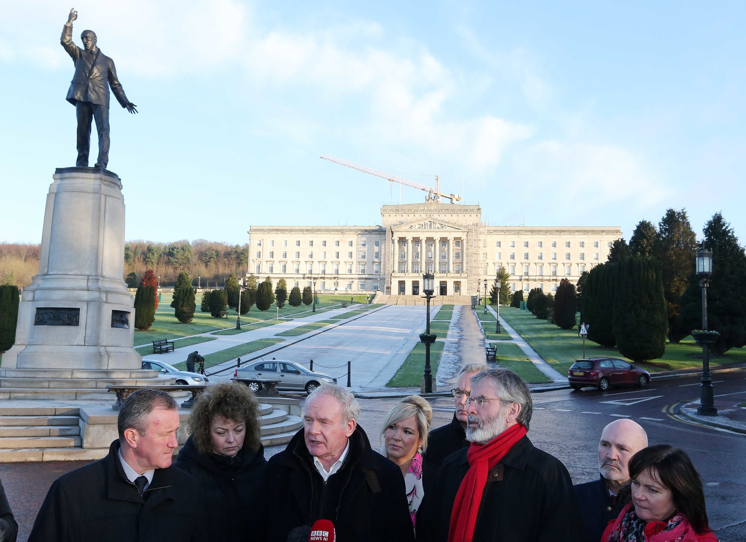 Sinn Féin representatives, including the late Martin McGuinness, holding a press conference next to Carson's statue in December 2014.