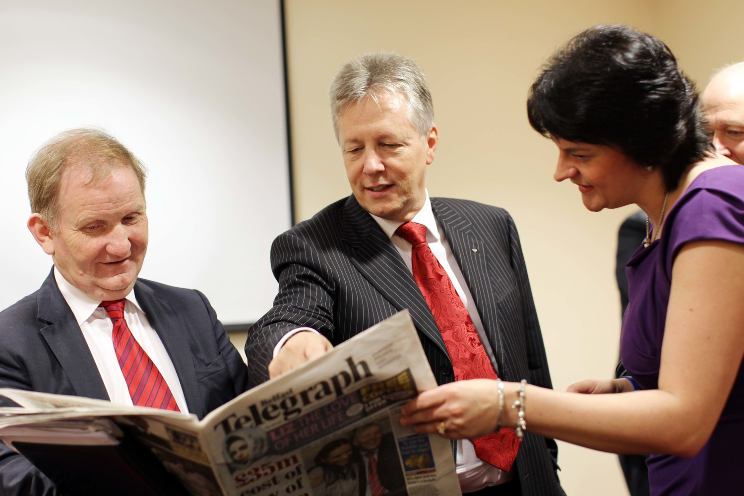 Peter Robinson and DUP colleagues reading the Belfast Telegraph