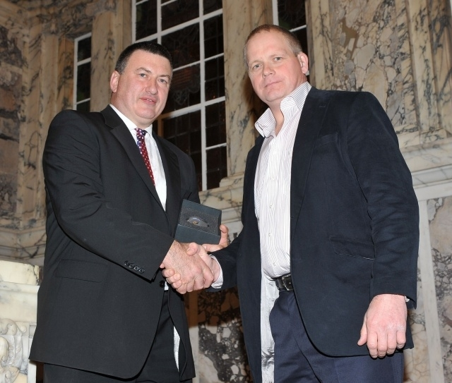Mark Langhammer receiving the IFA's Unsung Hero award from Trevor Ringland in 2009
